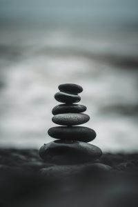 6 stones, precariously balanced on each other on the beach, with the ocean - fuzzy and out of focus - behind it.