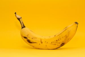 The is a picture of a scuffed up yellow banana on a banana yellow background.