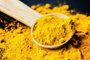 A pile of golden powdered turmeric with a wooden spoon in it, ready to use, for flavor and  anti-inflammatory properties
