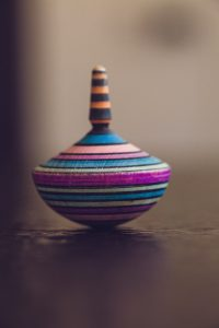 A picture of a spinning top, made out of different layers of dyed wood and shaped on a lathe. At least 33 by my count, of aqua, blue, lime green, fuschia, pale pink, peach, black, and brown. Kinda makes me want a top.