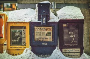 """Yellow, blue, and black newspaper boxes in drifted snow in China. """"Extree! Extree! Read all about it!"""""""