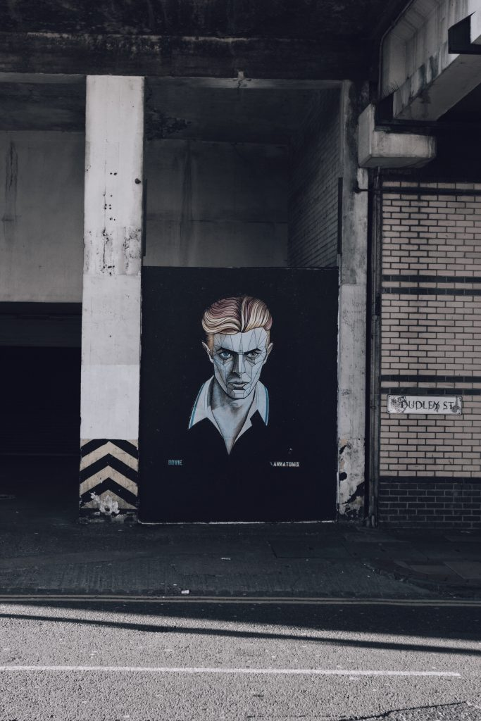 "A  city street (the sign says ""Dudley Street""), with a striking mural of David Bowie, Circa ""Early 80's', looking dapper, menacing, and stylish."