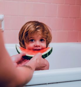Tow-headed kid in a pink tiled bath being fed a piece of watermelon. Heaven!