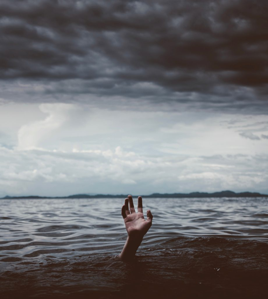a hand, reaching out of a stormy sea, with black clouds overhead