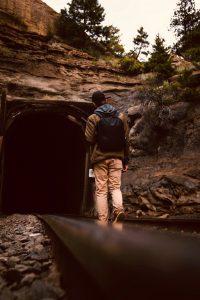 fella hiking into a mountain tunnel