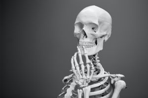 A skeleton in a pensive position contemplates the meaning of life and what to have for lunch